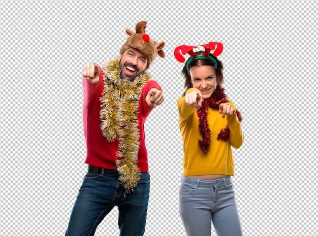 Couple habillé pour les vacances de noël pointe le doigt sur vous en souriant