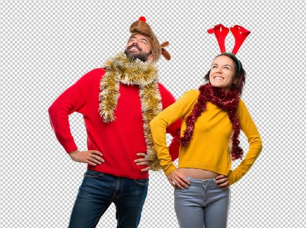 Couple habillé pour les vacances de noël, posant les bras à la hanche et riant