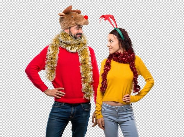 Couple habillé pour les vacances de noël, posant avec les bras à la hanche et souriant