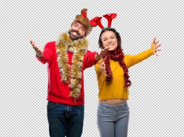 Couple habillé pour les vacances de noël présentant et invitant à venir. heureux que tu sois venu