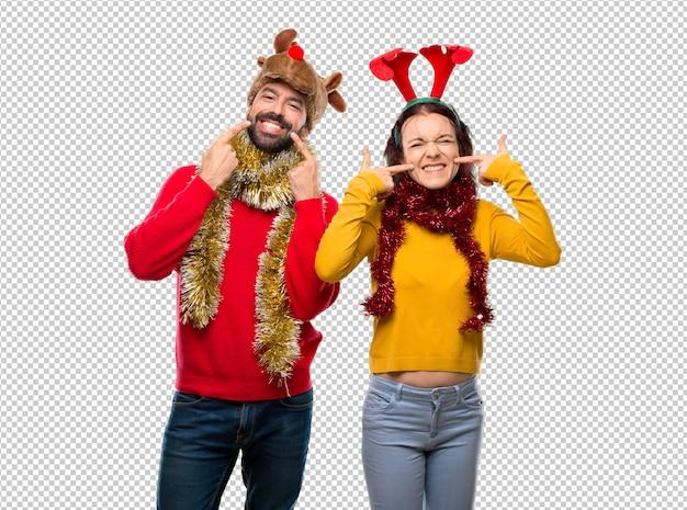 Couple habillé pour les vacances de noël souriant avec une expression agréable