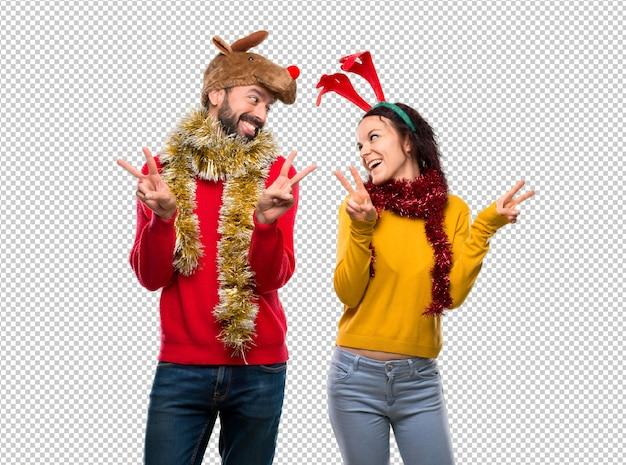 Couple habillé pour les vacances de noël souriant et montrant le signe de la victoire à deux mains