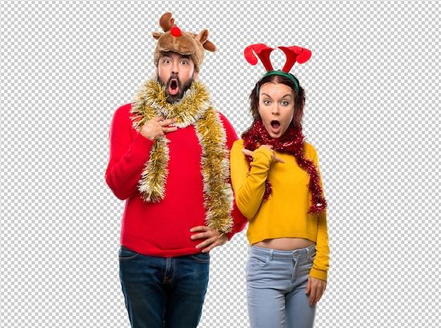 Couple habillé pour les vacances de noël surpris et choqué. émotion faciale expressive