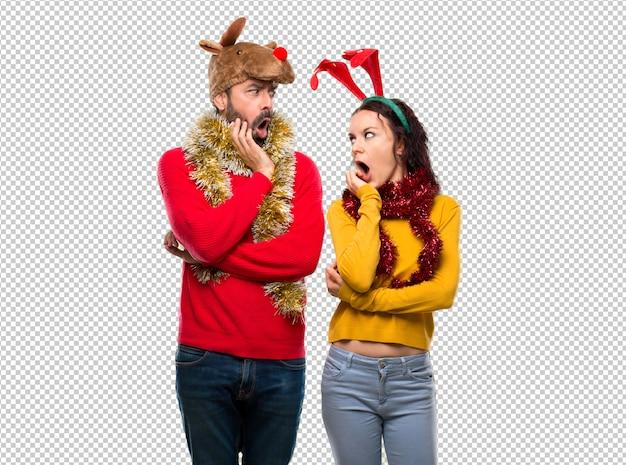 Couple habillé pour les vacances de noël surpris et choqué en regardant à droite