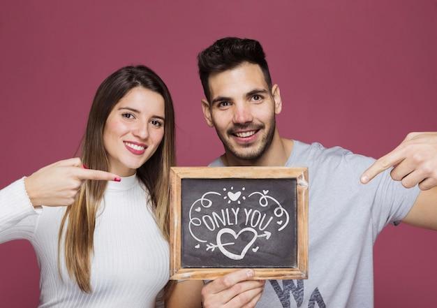 Couple présentant une maquette d'ardoise
