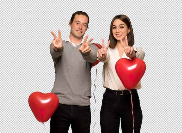 Couple en saint valentin souriant et montrant le signe de la victoire