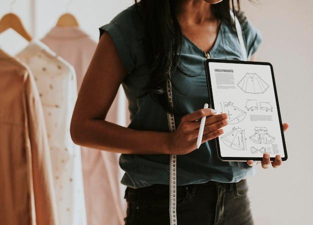 Créatrice de mode présentant son design sur une maquette de tablette numérique