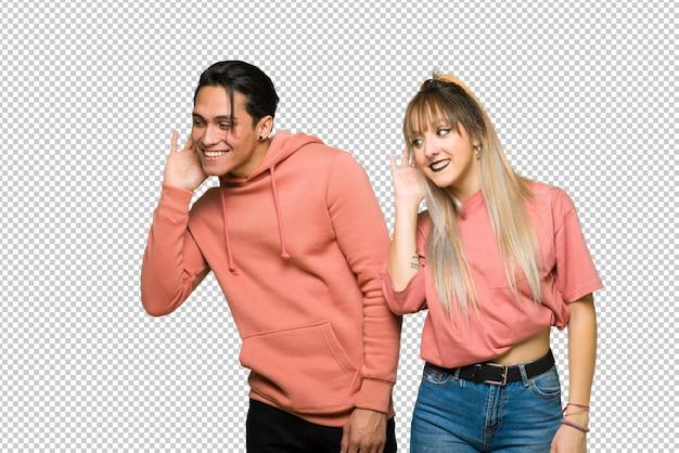 Dans la saint valentin jeune couple écoutant quelque chose en mettant la main sur l'oreille