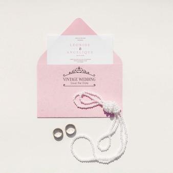 Décoration de mariage dans des tons roses avec enveloppe et anneaux de mariage