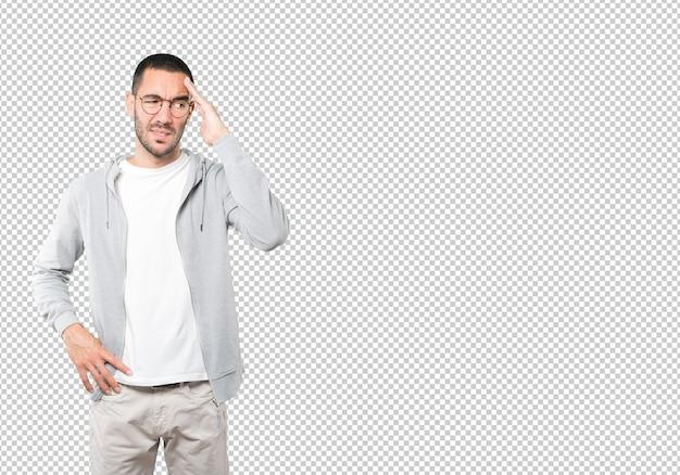 Déprimé jeune homme posant contre une surface transparente
