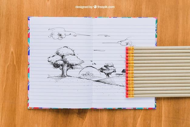 Dessin au crayon sur un cahier, des crayons et un fond en bois