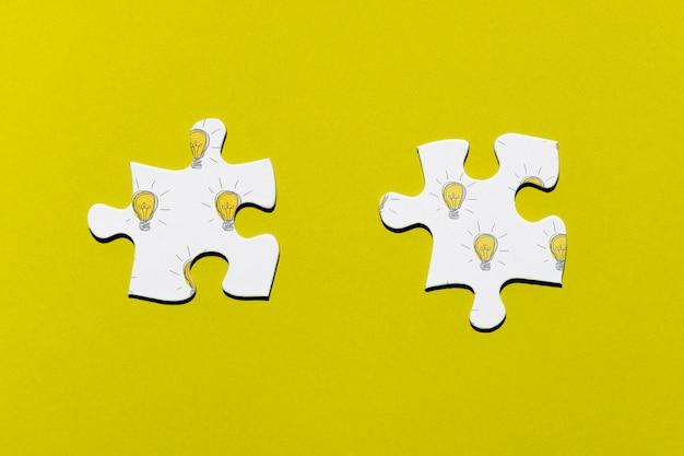 Deux pièces de puzzle sur fond jaune