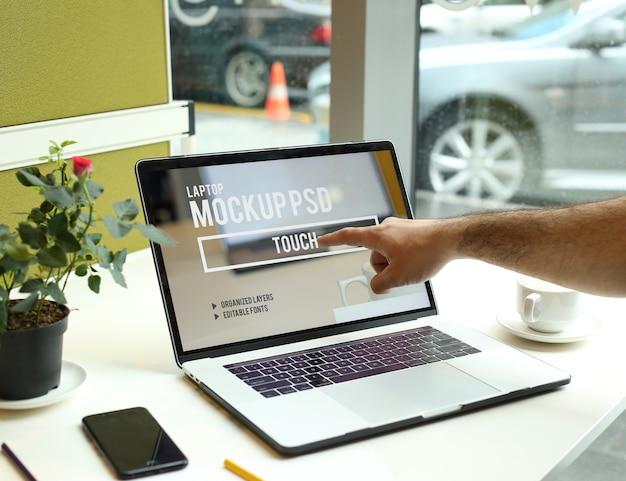 Doigt touchant l'ordinateur portable dans l'espace de travail à la maquette de bureau psd