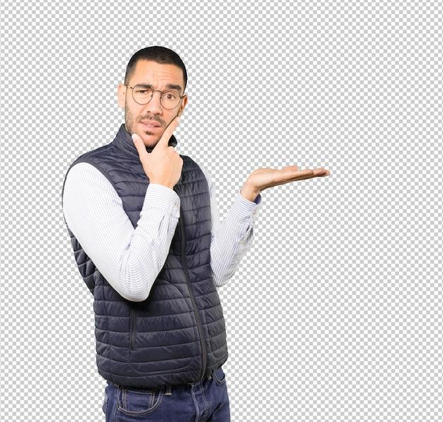Douteux jeune homme tenant quelque chose avec sa main