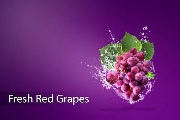 Éclaboussures d'eau sur des raisins rouges frais sur fond rouge.