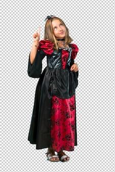 Enfant blonde habillée comme un vampire pour les fêtes d'halloween en comptant le signe numéro un