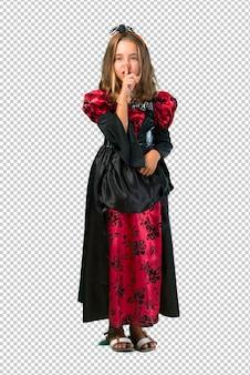 Enfant blonde habillée en vampire pour les vacances d'halloween montrant un signe de fermeture de la bouche