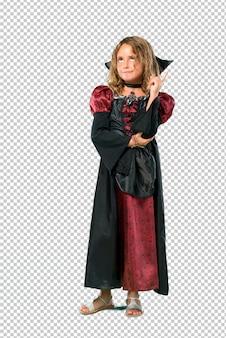 Un enfant habillé en vampire lors des fêtes d'halloween montrant avec l'index une bonne idée