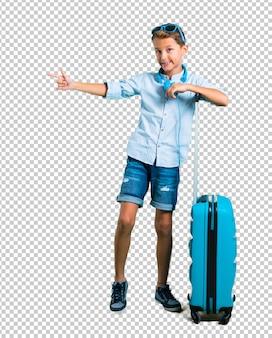 Enfant avec des lunettes de soleil et un casque voyageant avec sa valise un doigt pointé sur le côté