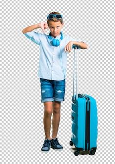 Enfant avec des lunettes de soleil et un casque voyageant avec sa valise montrant le pouce vers le bas