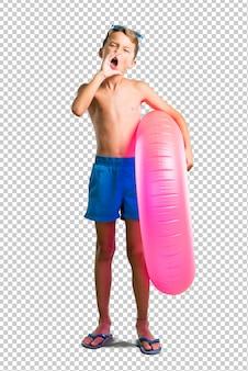Enfant en vacances d'été criant avec la bouche grande ouverte
