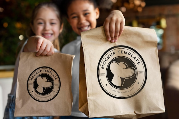 Enfants de plan moyen tenant des sacs de nourriture