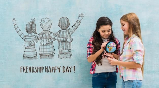 Enfants tenant un globe terrestre avec maquette du mur