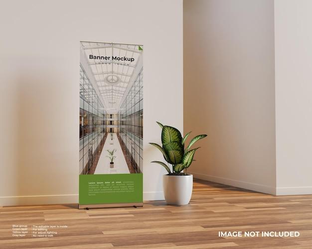 Enroulez la maquette de la bannière dans la scène intérieure avec une plante à côté