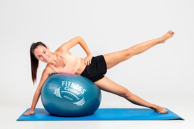 Entraînement de femme plein coup avec ballon de fitness