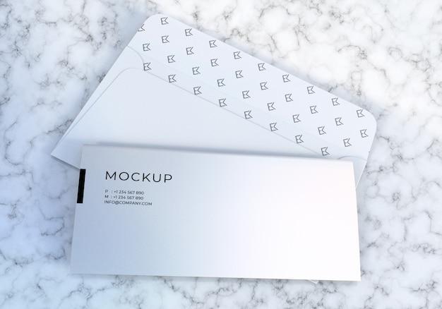 Enveloppe blanche propre et papier à en-tête mis en fond de texture de marbre maquette