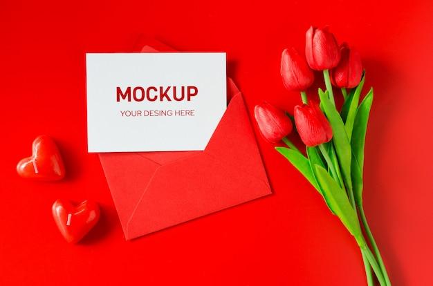 Enveloppe rouge avec papier vierge, bouquet de tulipes et bougies en forme de coeur.