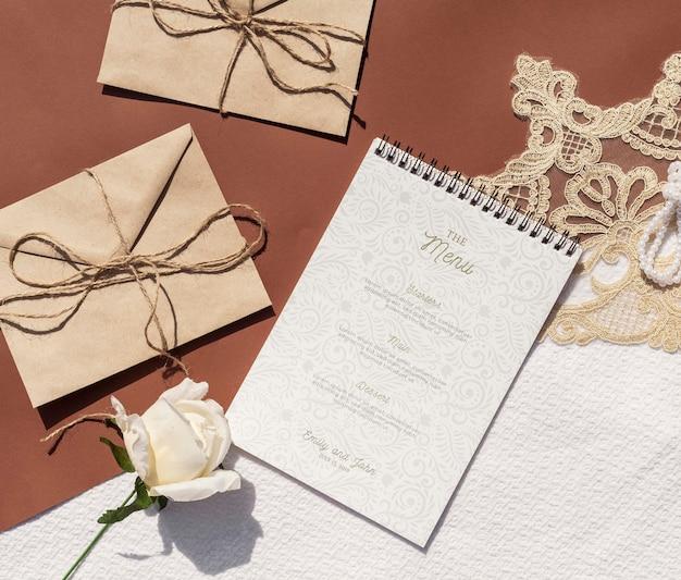 Enveloppes en papier brun avec rose et bloc-notes