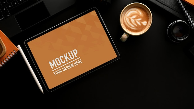 Espace de travail avec maquette de tablette numérique, tasse à café et fournitures de bureau dans la salle de bureau à domicile