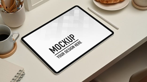 Espace de travail avec maquette de tablette numérique, tasse à café et fournitures