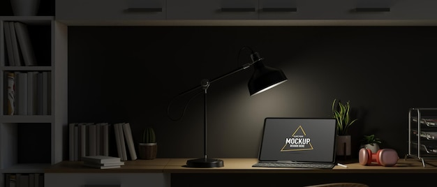 Espace de travail la nuit avec ordinateur portable ouvert et lumière de la lampe de table travail de nuit espace de travail sombre