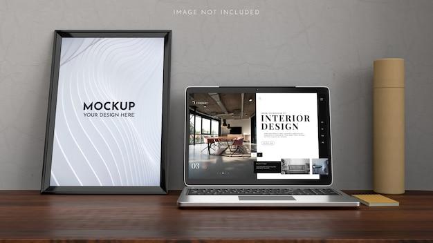 Espace de travail avec un ordinateur portable, des affiches, une maquette de cadre en design d'intérieur.