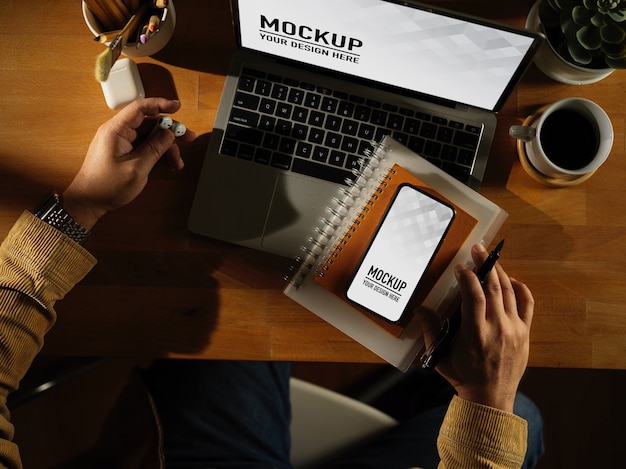 Espace de travail avec téléphone numérique et maquette d'ordinateur portable avec tasse