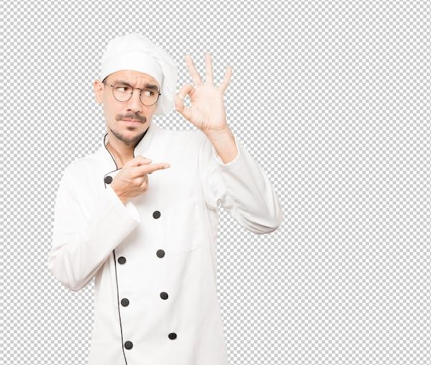 Étonné jeune chef utilisant ses mains comme des jumelles