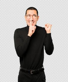 Étonné jeune homme demandant le silence en faisant des gestes avec son doigt