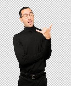 Étonné jeune homme faisant un geste d'appel avec la main