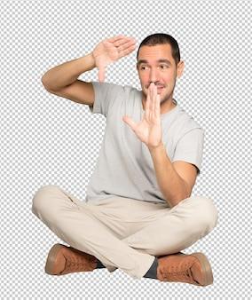 Étonné Jeune Homme Faisant Un Geste De Prendre Une Photo Avec Les Mains PSD Premium