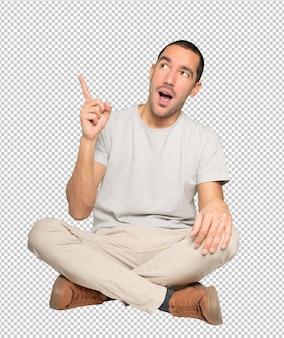 Étonné jeune homme pointant vers le haut avec son doigt