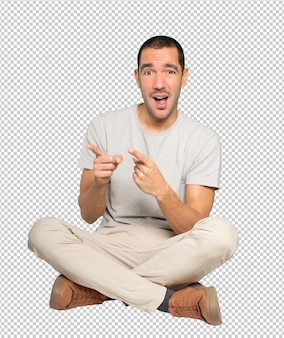 Étonné jeune homme pointant vers vous avec son doigt