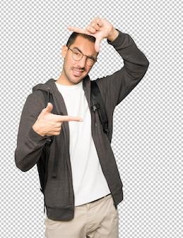Étudiant étonné faisant un geste de prendre une photo avec les mains