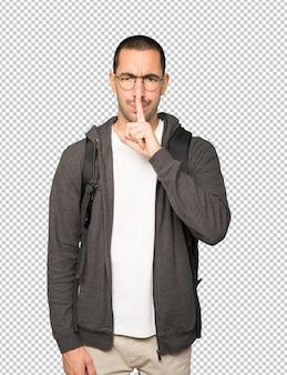 Étudiant sérieux demandant le silence en faisant des gestes avec son doigt