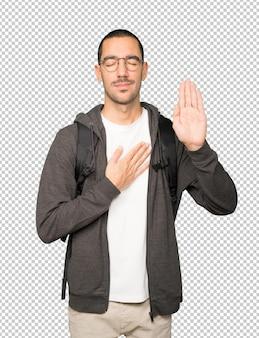 Étudiant sérieux avec un geste de serment