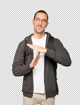Étudiant stressé faisant un geste de temps mort avec ses mains