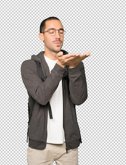 Étudiant sympathique faisant un geste d'envoyer un baiser avec sa main