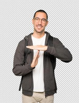Étudiant sympathique faisant un geste de temps mort avec ses mains