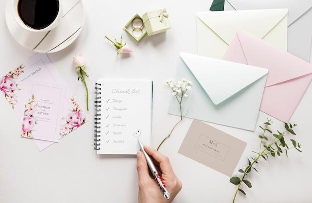 Fat lay de carnet de mariage avec enveloppes et fleurs